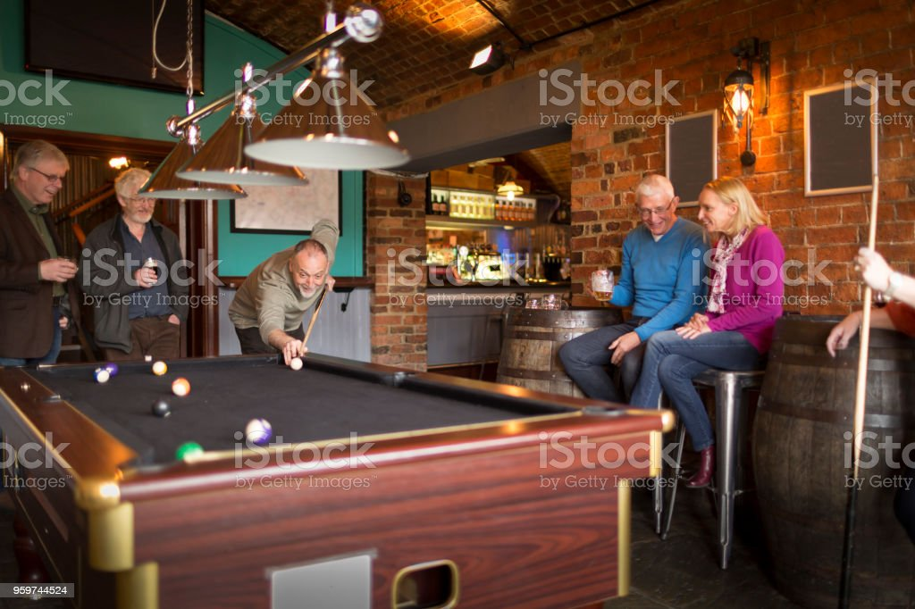 A group of friends playing pool in a bar stock photo