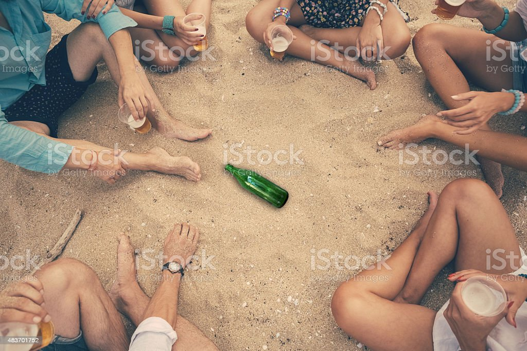 Group of friends playing spin the bottle at the beach stock photo
