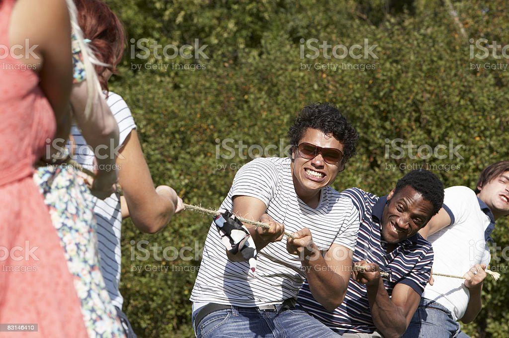Group of friends playing tug of war royalty free stockfoto