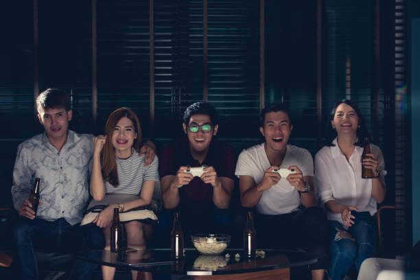 gruppe von freunden spielen von videospielen im fernsehen zu hause. - spielabend snacks stock-fotos und bilder