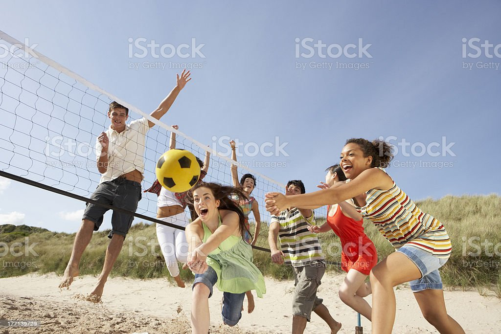 Group of friends playing volleyball on the beach stock photo