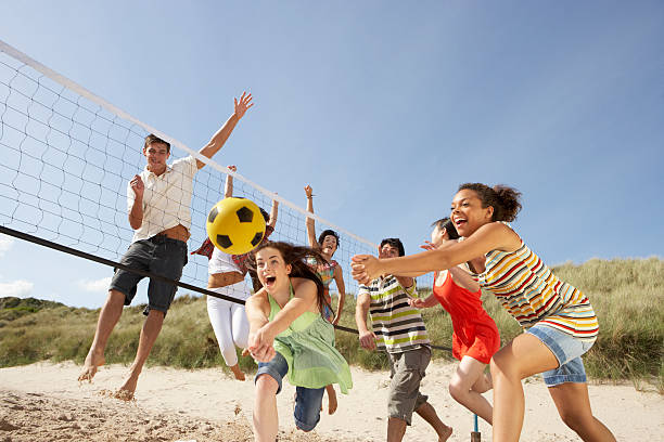 group of friends playing volleyball on the beach - volleyball sport stock photos and pictures