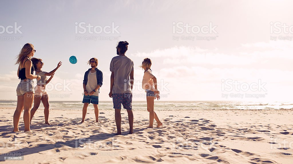 Group of friends playing with ball at beach stock photo