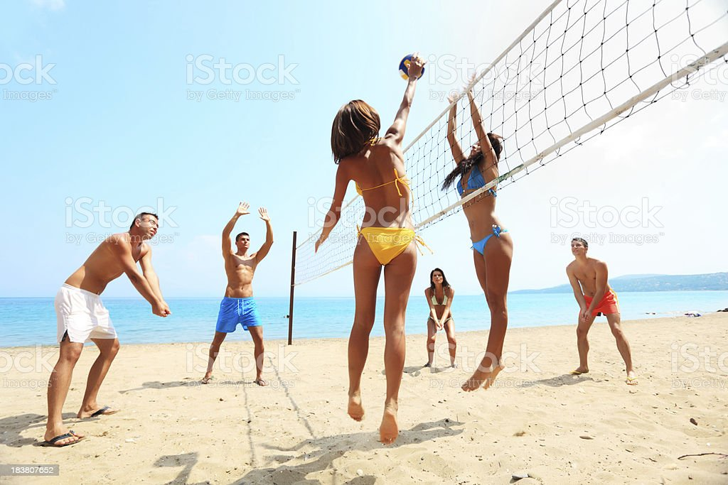 Groupe d'amis jouer au volley-ball sur la plage. - Photo