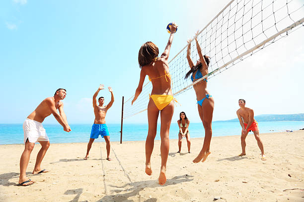 Group of friends plays volleyball on the beach. stock photo