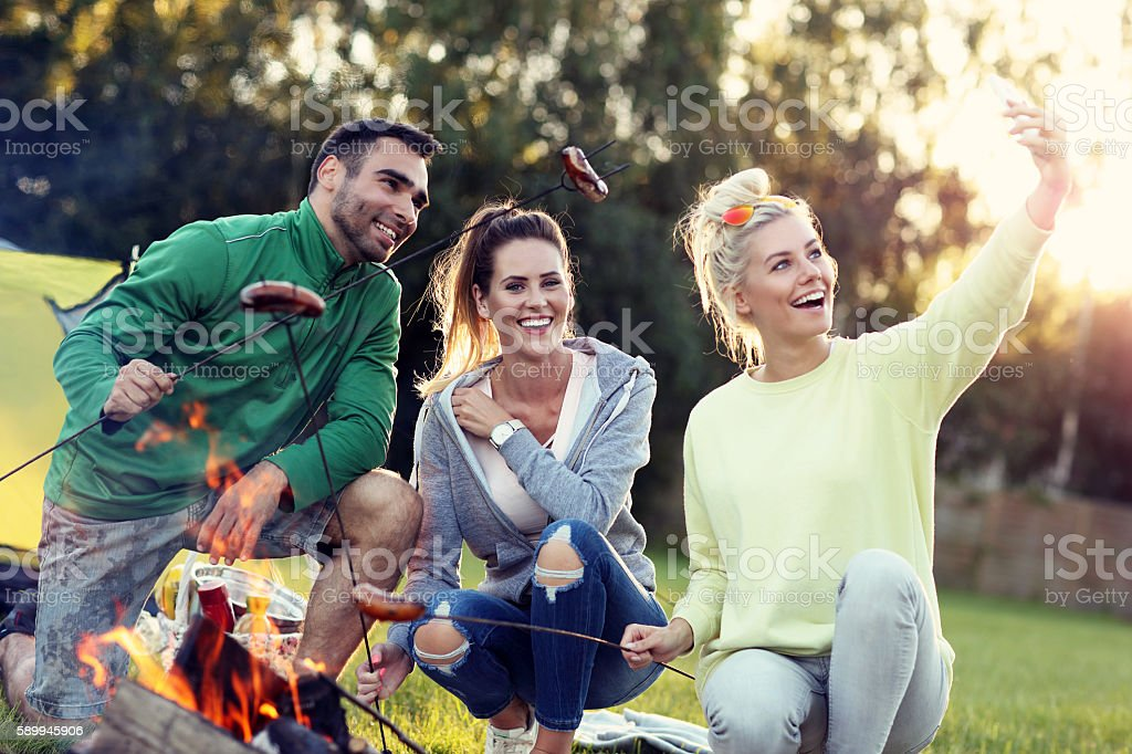 Group of friends preparing sausages on campfire stock photo