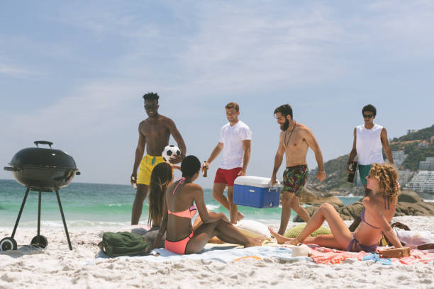 Group of friends relaxing and enjoying at beach stock photo