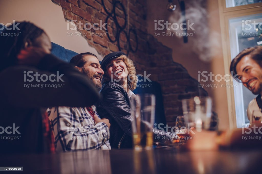 Group of friends relaxing in bar Multi ethnic group of friends sitting in a pub, drinking beer. Adult Stock Photo