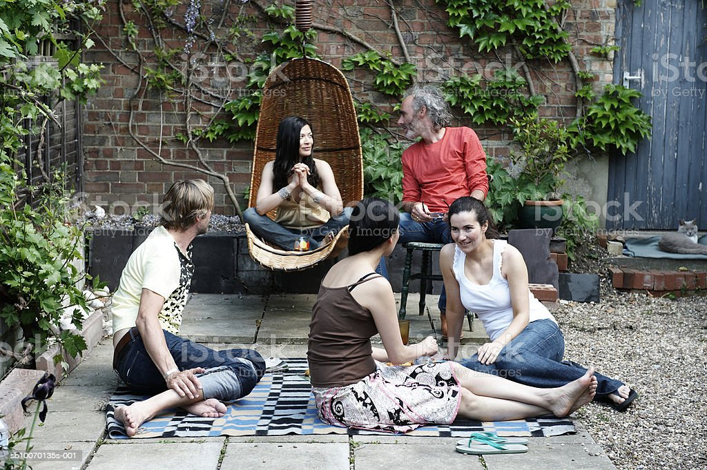 Group of friends relaxing in courtyard royalty-free stock photo