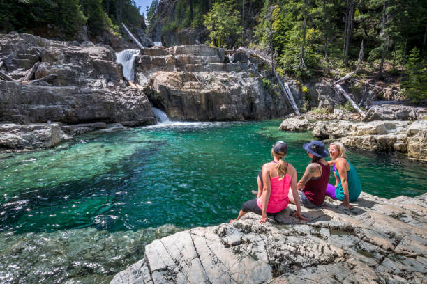 Group of friends resting by waterfalls. Three young women sitting on edge cliff by natural water pool. vancouver island stock pictures, royalty-free photos & images