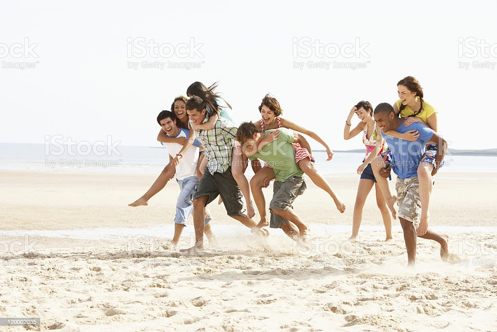 Group Of Friends Running Along Beach Together stock photo