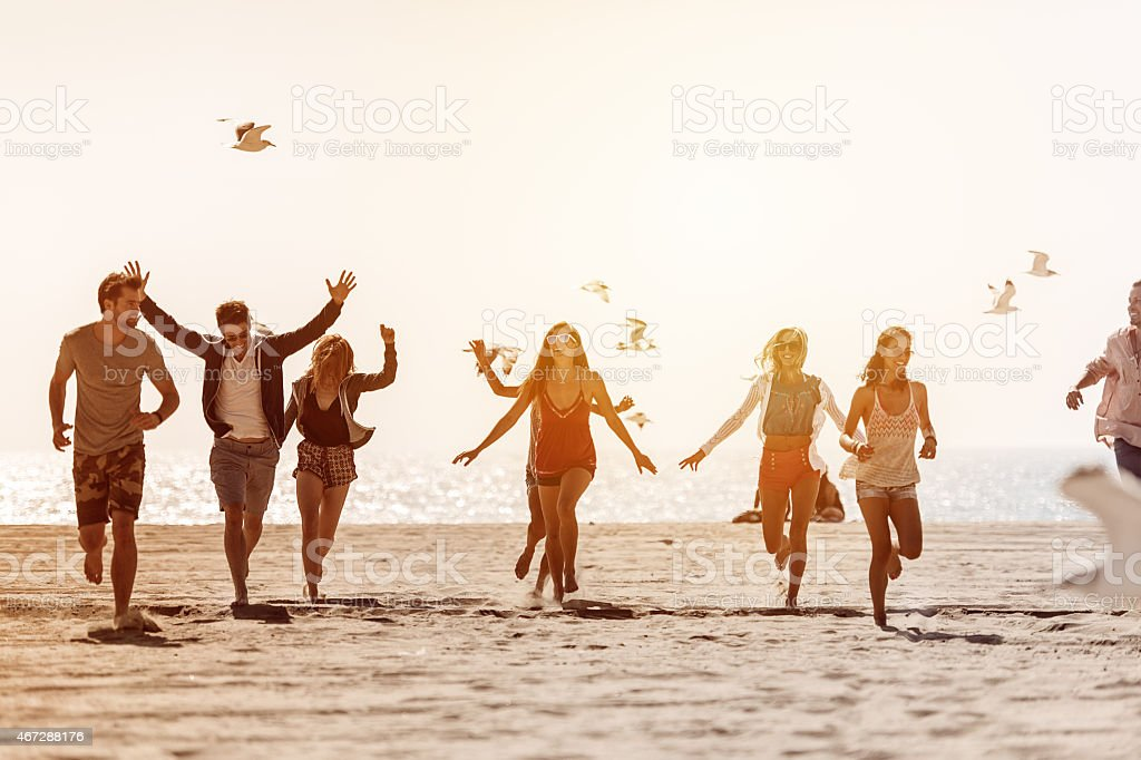 Group of friends running at the beach stock photo