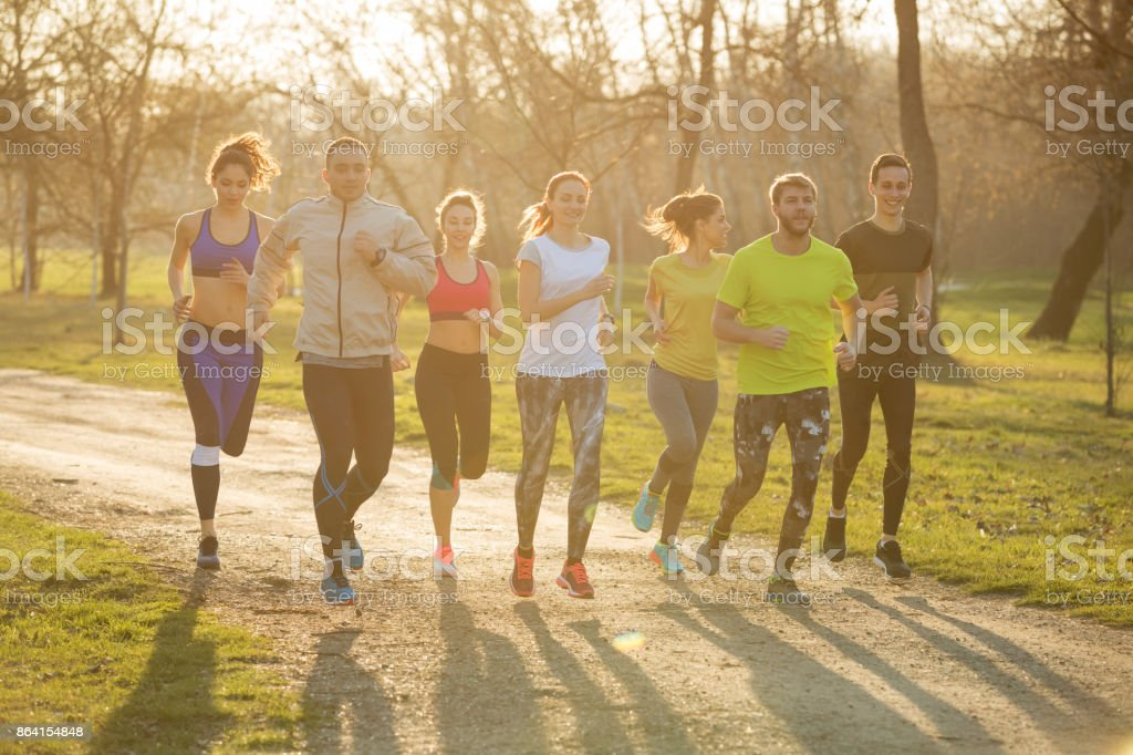 Group of friends running in park royalty-free stock photo