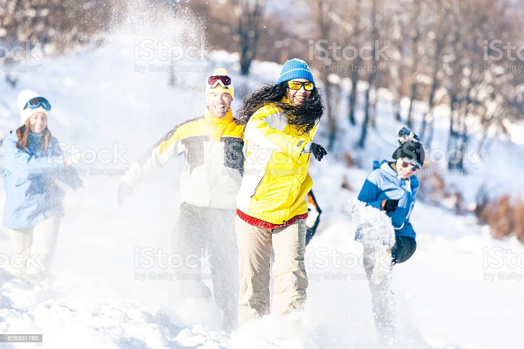 Group of friends running on snow path stock photo