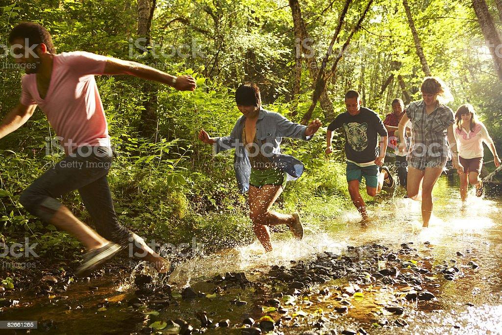 Group of friends running through stream stock photo