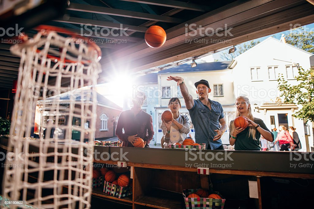 Group of friends shooting hoops at the fair - Photo