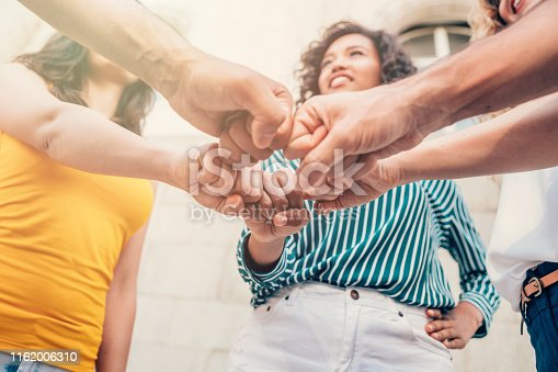 Stack of hands, friends showing unity.