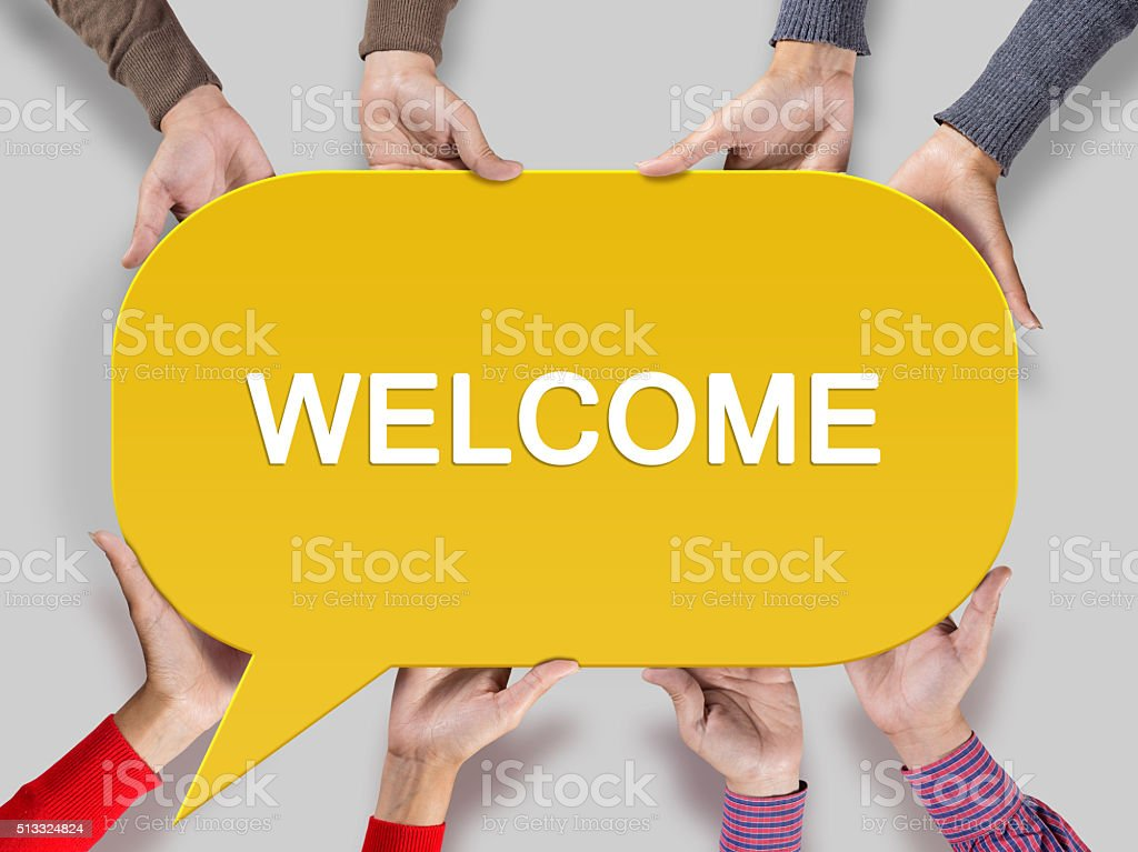 Group of friends showing welcome sign on speech bubble stock photo