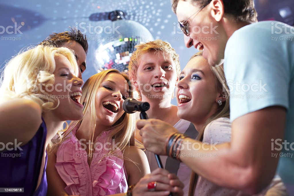 Group of friends singing into a mic on karaoke night stock photo