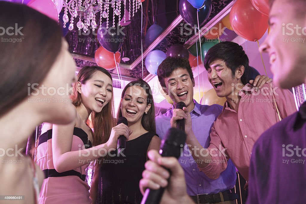 Group of friends singing together karaoke stock photo