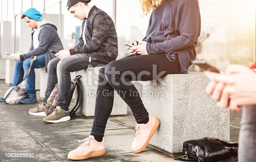 istock Group of friends sitting and using smartphone at university college backyard break - Guys and girls addicted by mobile smart phone - Technology concept with always connected millennials - Filter image 1063555892