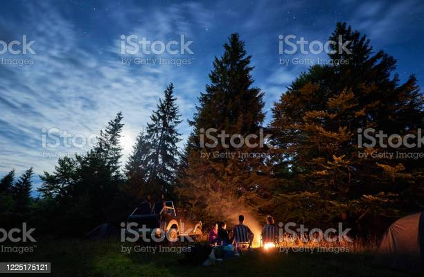 Photo of Group of friends sitting around a bonfire on a green mountain meadow surrounded by spruce trees under starry sky