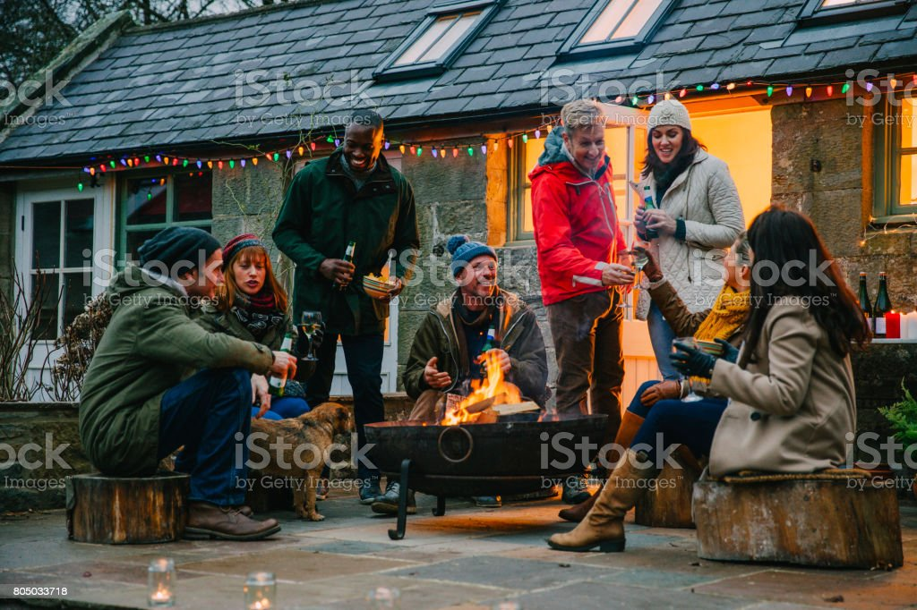 Group of Friends Sitting Around a Fire Pit stock photo