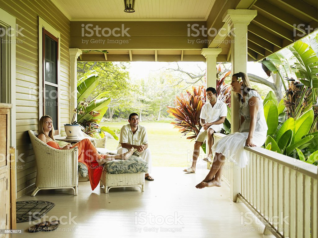 Group of friends sitting on front porch laughing Lizenzfreies stock-foto
