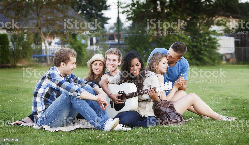 Group of friends sitting on grass hanging out. royalty-free stock photo
