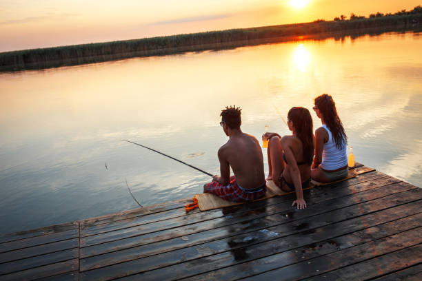 Group of friends sitting on pier by the lake and fishing. stock photo