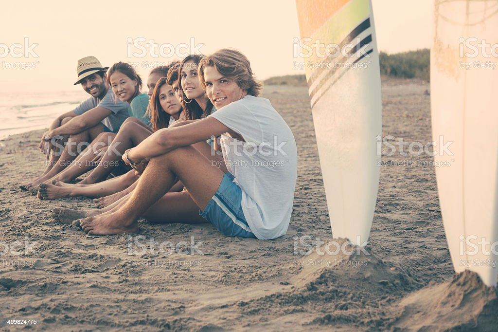 Group of friends sitting on sand next to two surf boards stock photo