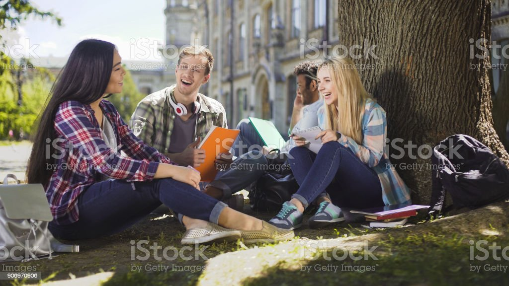 Gruppe von Freunden sitzen unter Baum miteinander Lachen, miteinander zu reden – Foto