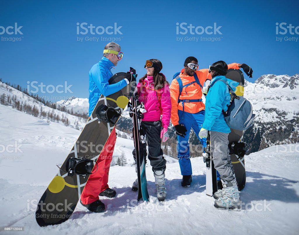 Group of friends skiing and snowboarding stock photo