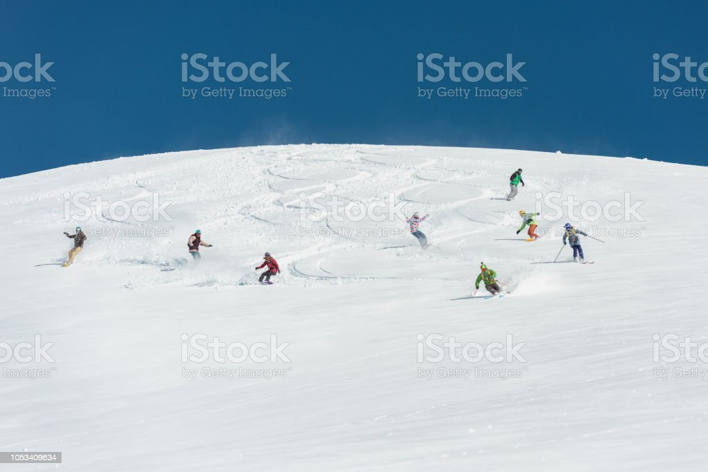 Group of friends skiing and snowboarding together in fresh powder snow