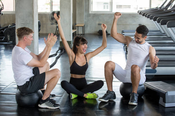 group of friends sport people celebrate and raising hands to success  after exercise in  gym . young fitness  in sportswear take a break from workout healthy stock photo