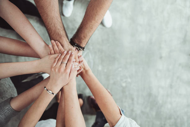 Group of friends stack their hands together, teamwork concept stock photo