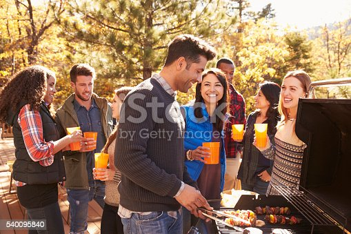 istock Group of friends stand at a barbecue, one cooking at grill 540095840