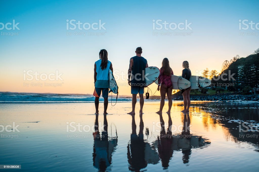 Group of friends standing at the sandy beach with surfboards stock photo