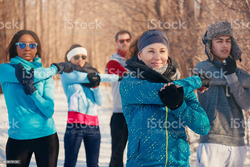 Group of friends stretching in the snow in winter – Foto