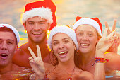 Group of friends swimming with Santa hats.  Summer Christmas fun in a warm climate. The group of young people look like they are on vacation in a tourist resort. They are all in swimwear at sunset with some lens flare.