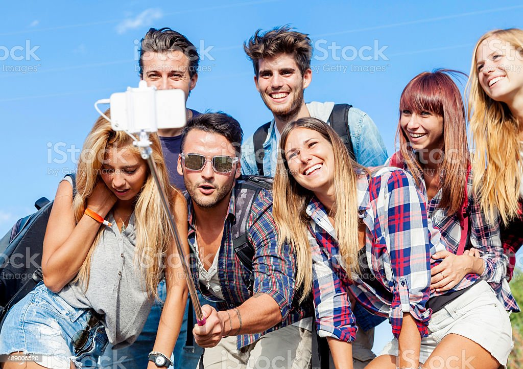 group of friends taking a self portrait with selfie stick stock photo
