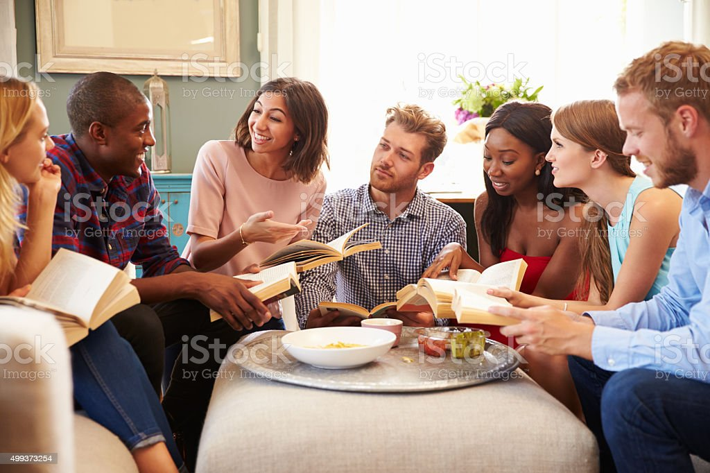 Group Of Friends Taking Part In Book Club At Home stock photo