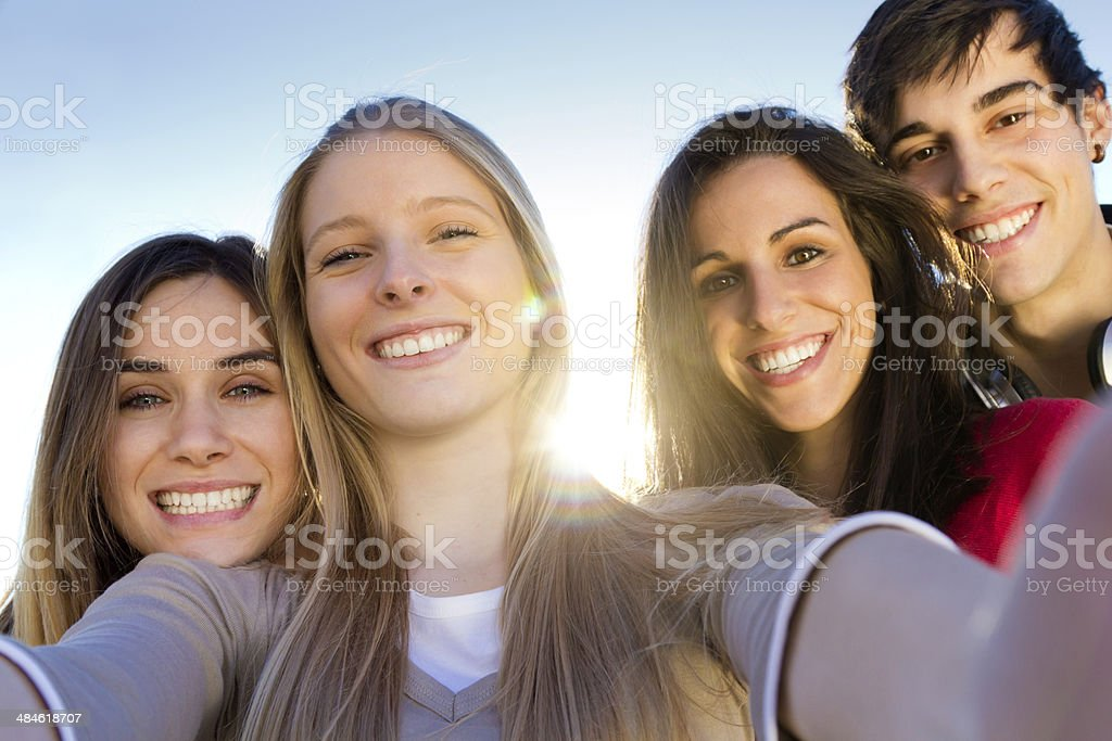 Group of friends taking photos with a smartphone stock photo