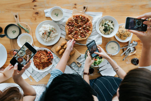 group of friends taking pictures of food on the table with smartphones during party - foodie stock photos and pictures