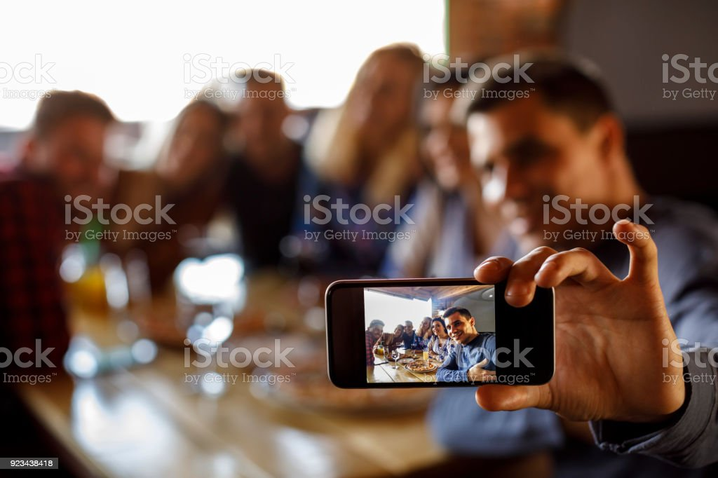 Group of friends taking selfie at a restaurant stock photo