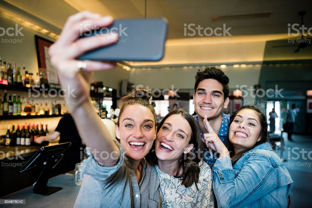 Group of friends taking selfie in bar, smiling stock photo