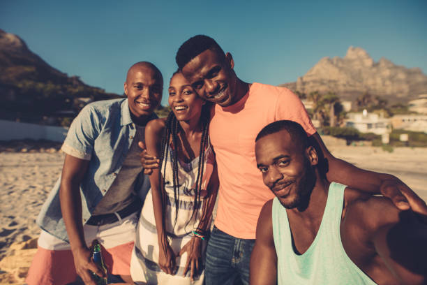 Group of friends taking selfie on the seashore. stock photo