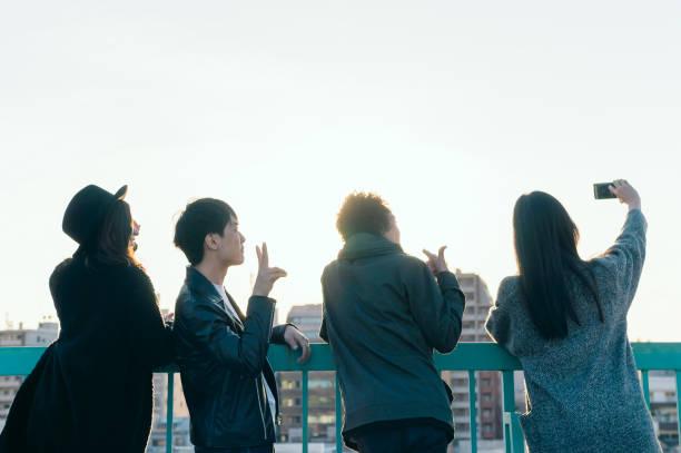 groupe d'amis prenant selfie urbain sur le toit - génération z photos et images de collection