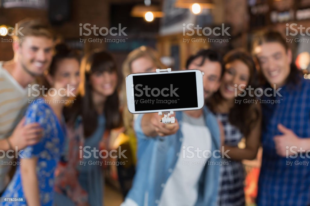 Group of friends taking selfie through mobile phone royalty-free stock photo