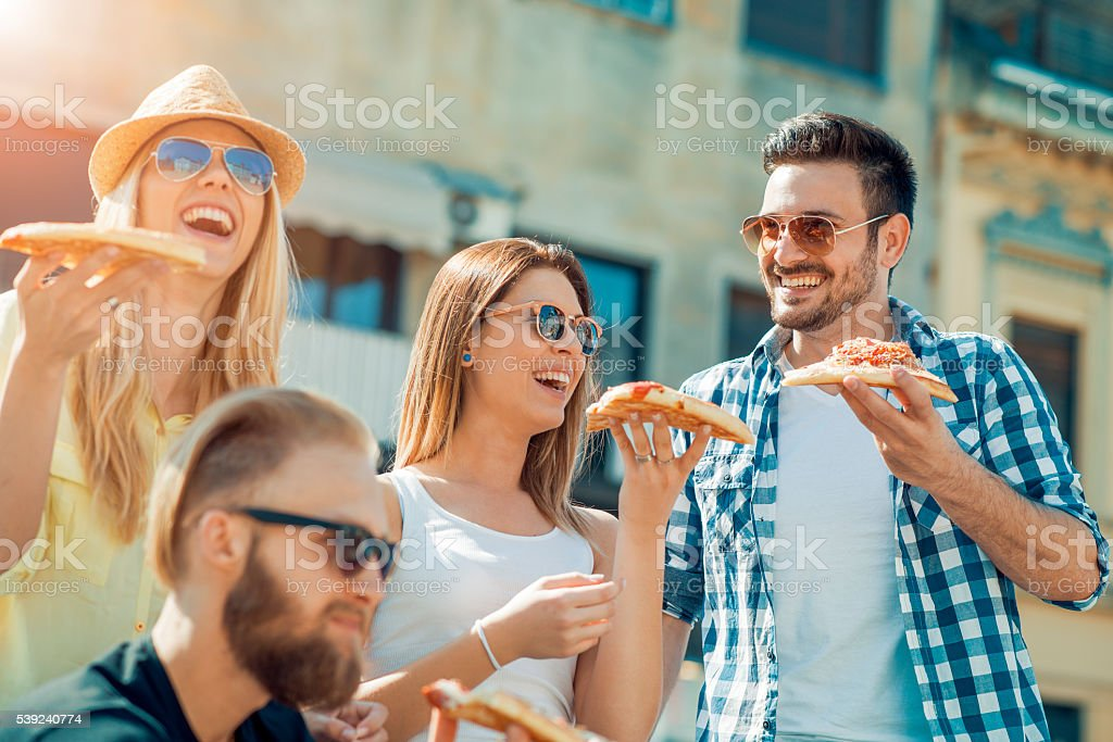 Group of friends taking their slices of pizza royalty-free stock photo